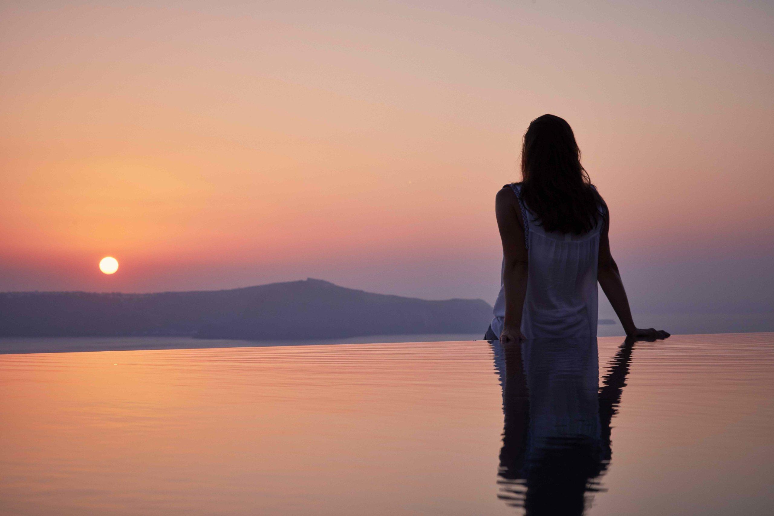 Femme regardant le coucher de soleil sur la piscine à débordement