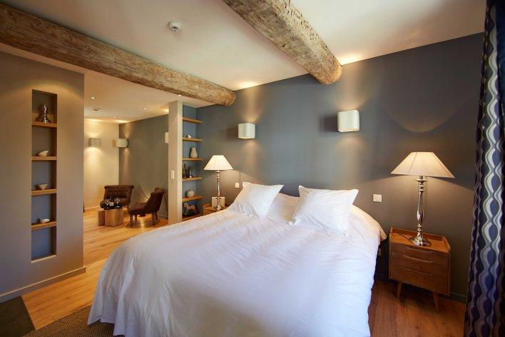 Chambre lit double, linge de lit blanc, murs gris, poutres apparentes