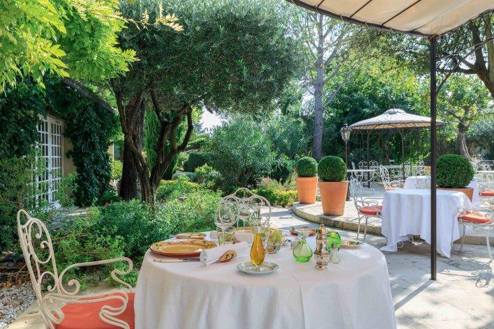 Terrasse table fer forgé et petits buissons