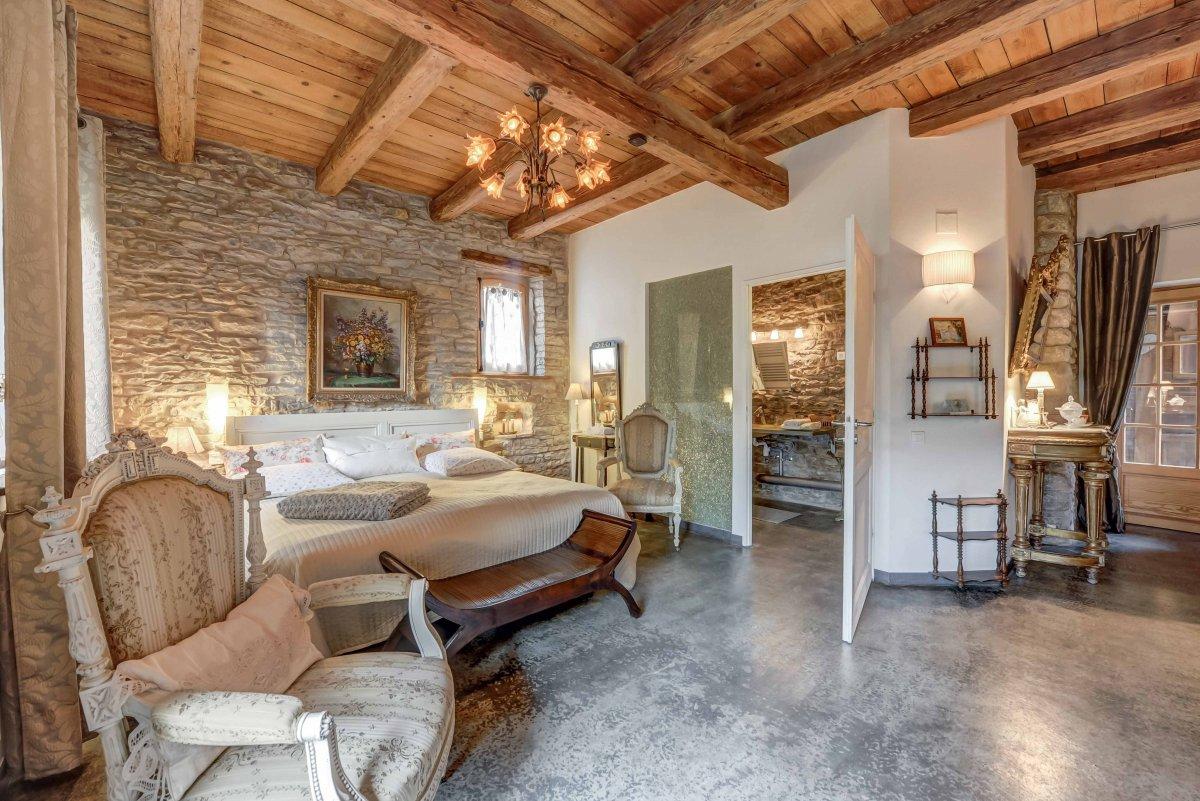 Chambre avec poutre apparente et mur en pierre