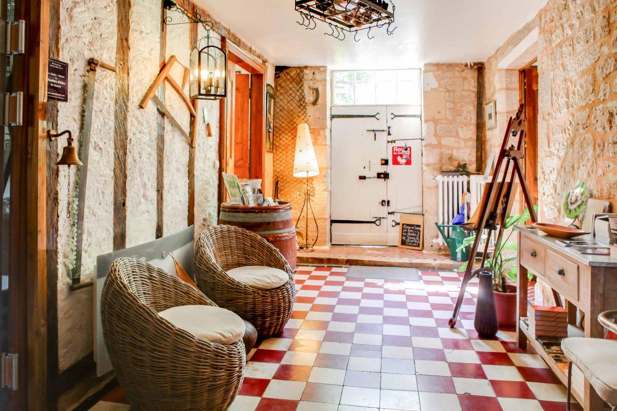 Entrée avec mur en colombage, sol carreaux rouge et blanc et fauteuils en osiers