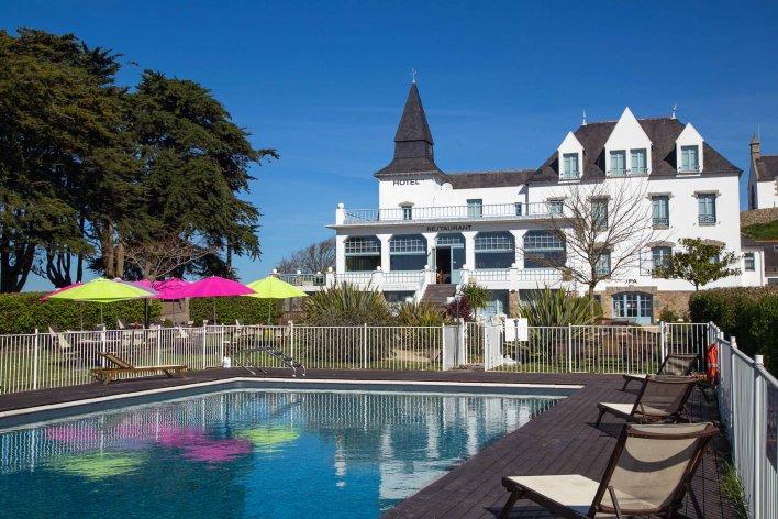 Grande piscine avec transat, devant grand hôtel avec restaurant