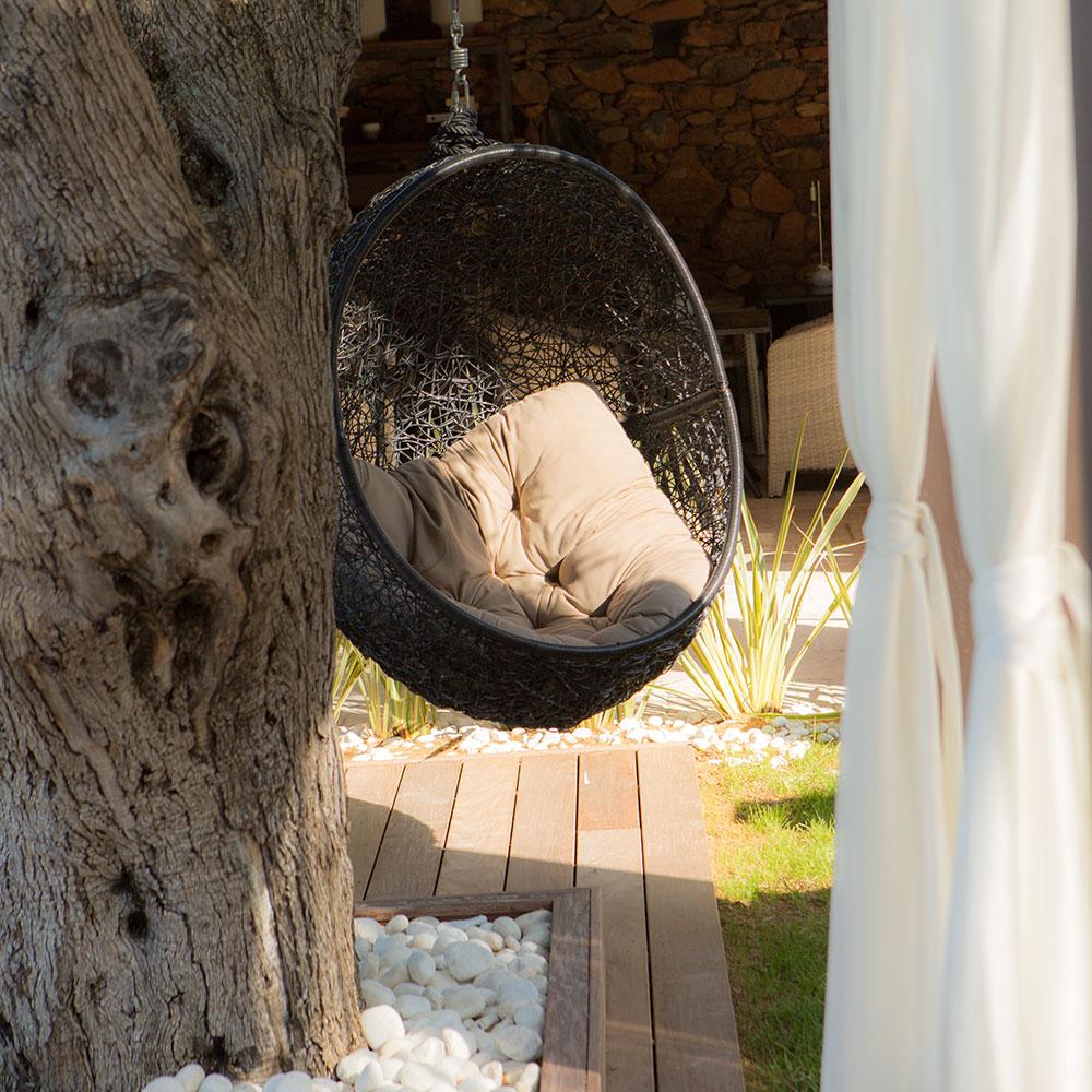 Fauteuil oeuf suspendu haut dessus d'une terrasse en bois