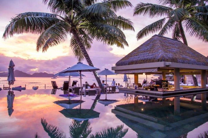 piscine à débordement devant la mer et les palmiers aux Seychelles