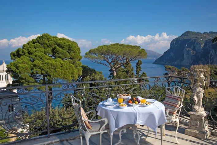 Terrasse avec table et petit déjeuner vue sur mer.