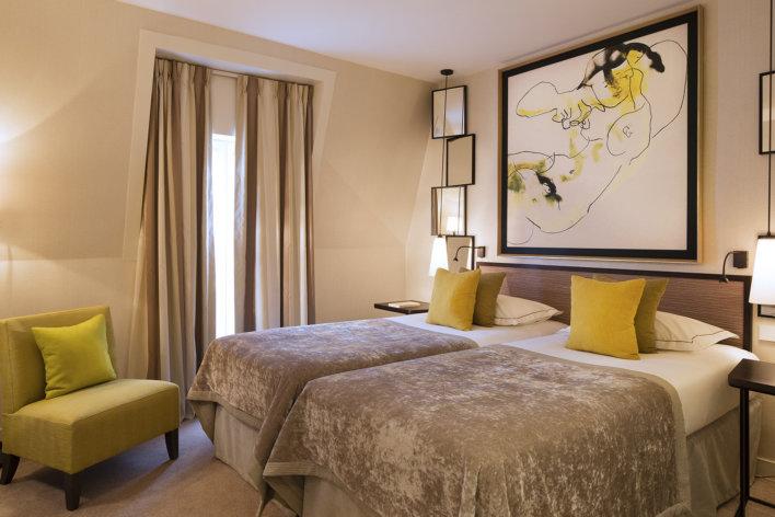 Chambre deux lit une place décoration jaune et taupe cadre en tête de lit