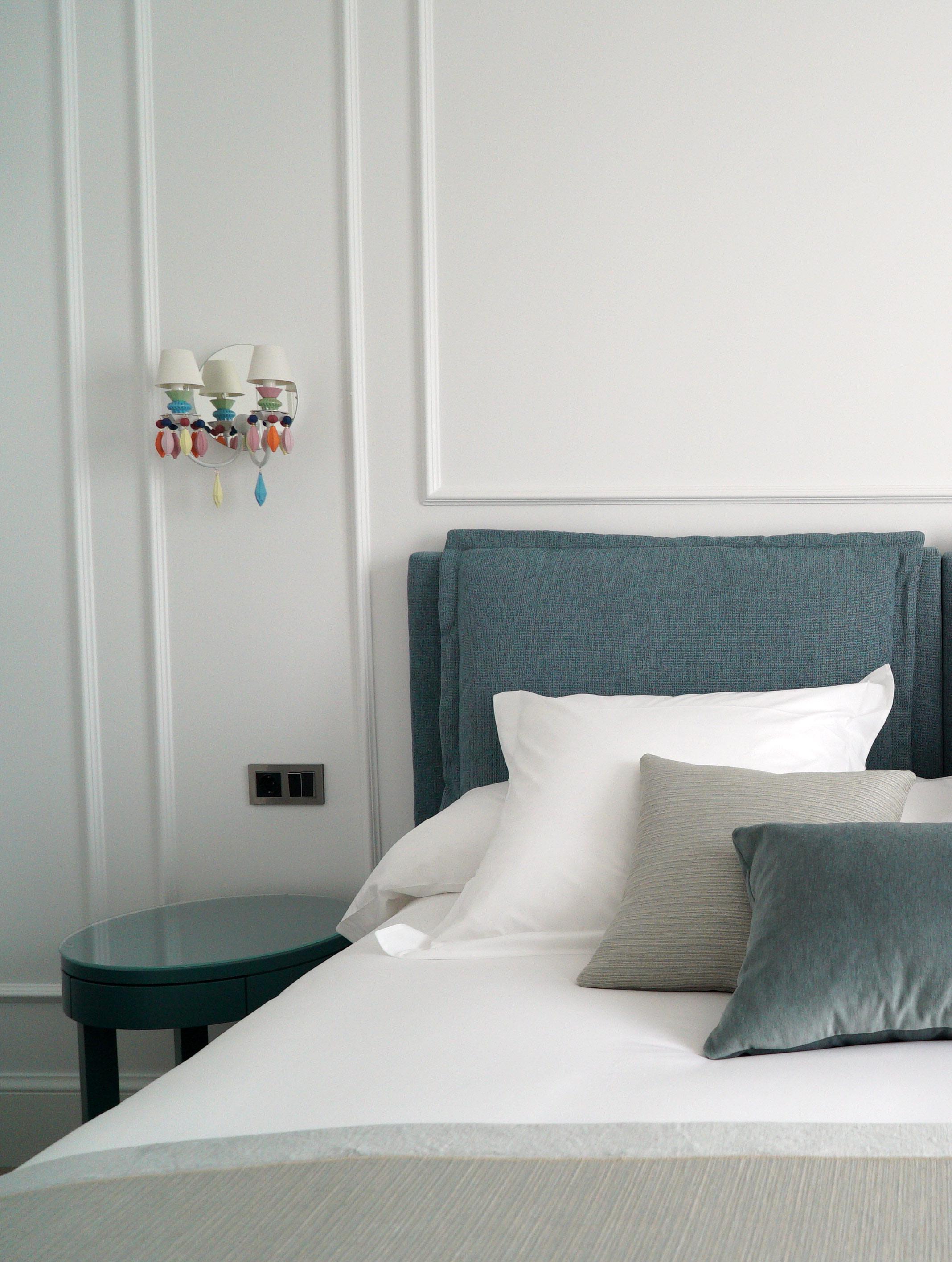 Détail tête de lit coussin bleu gris blanc et suspension colorée