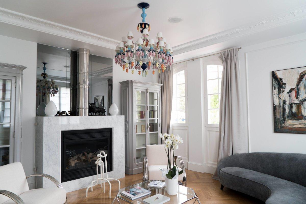 grand salon cheminée blanche, canapé gris, lustre coloré et meubles design
