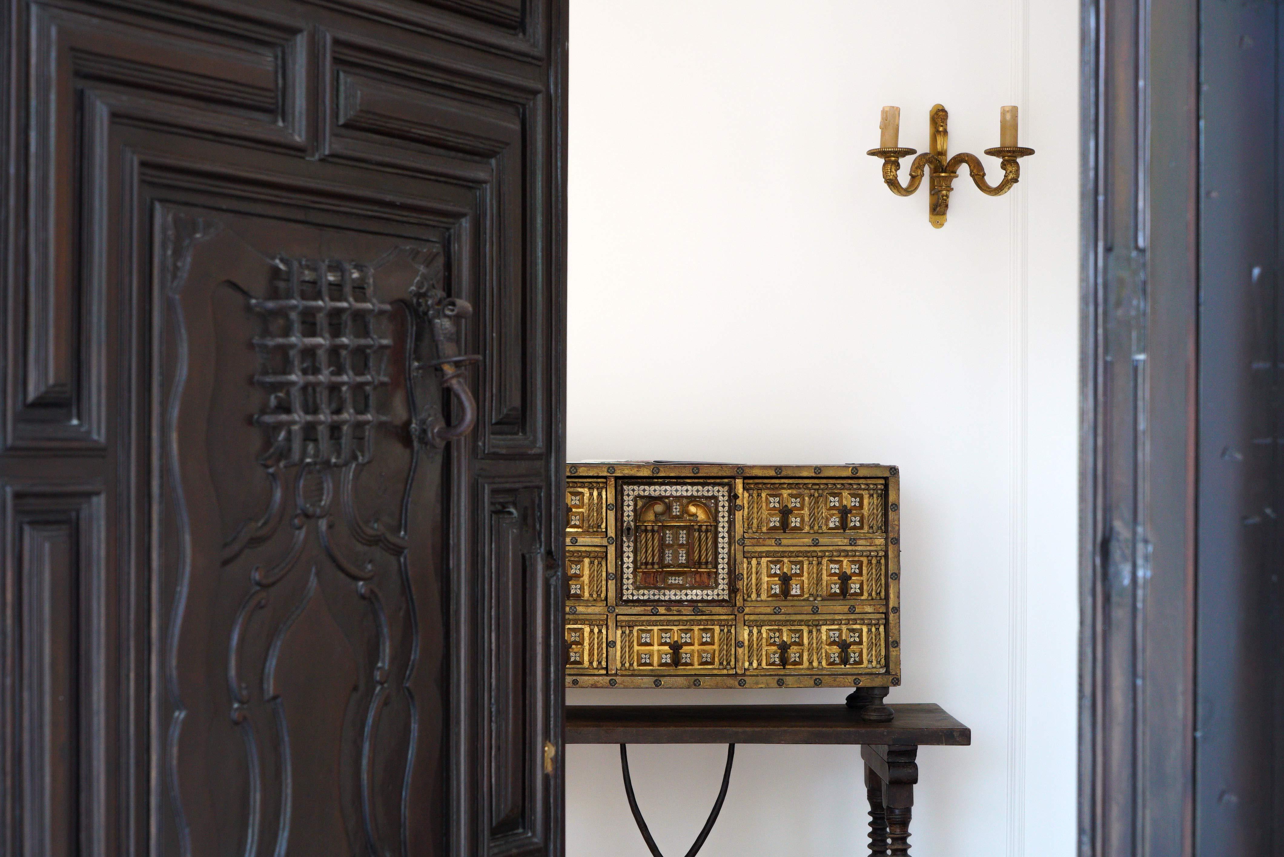 Photo détail coffret dorée derrière porte en bois massif