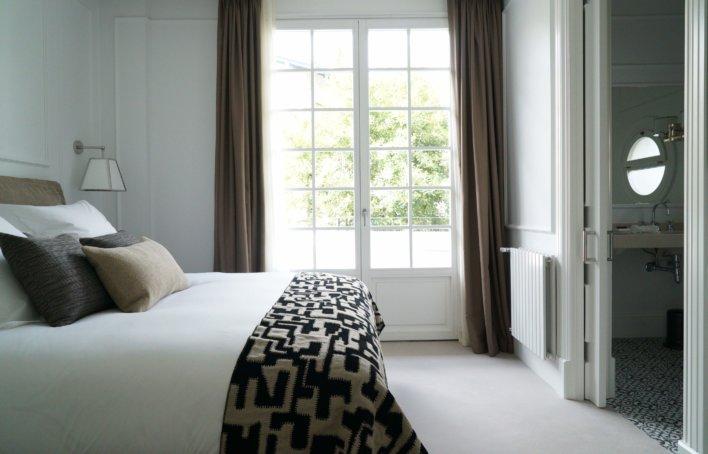 Chambre lit double ton neutre et grande porte fenêtre