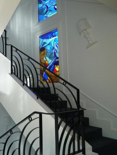 escalier blanc, rembarre fer forgé noir et vitraux aux murs