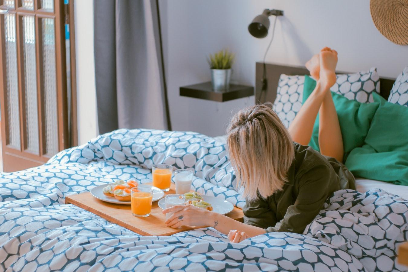 une femme prend son petit déjeuner au lit