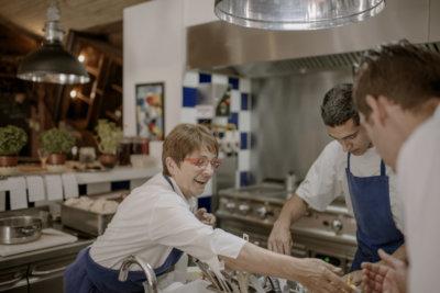 Photo d'une femme chef et de deux cuisinier en cuisine en tablier bleu