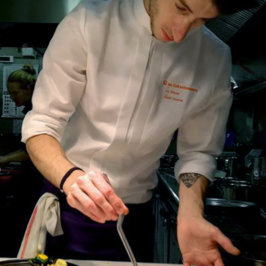Photo de chef en veste de cuisine pendant le dressage d'un plat