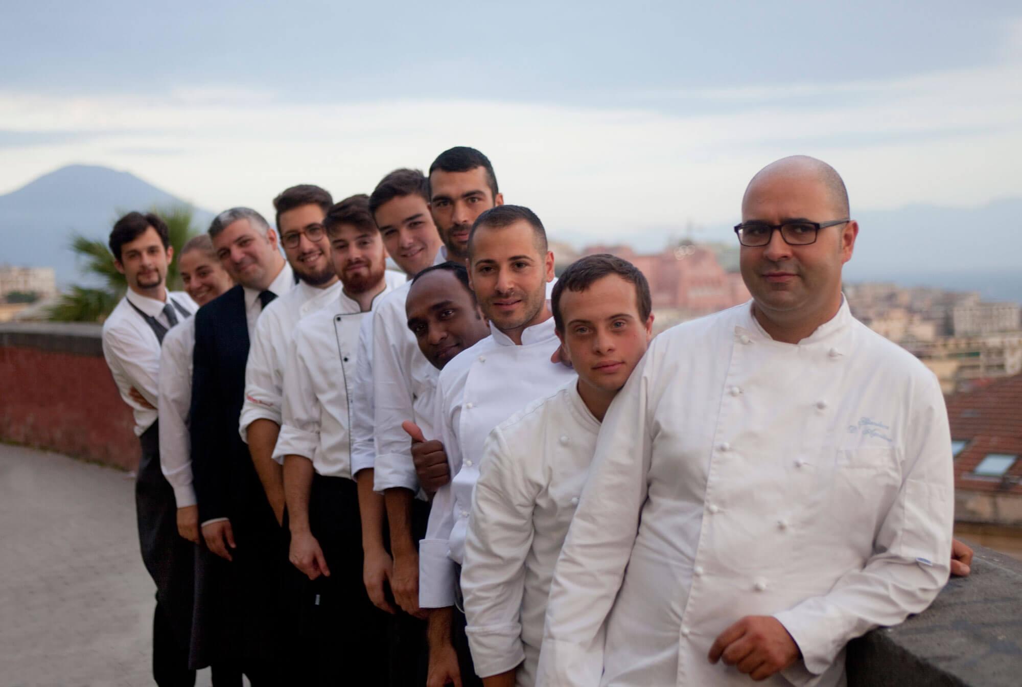 Personnel d'un restaurant photographié devant le Vésuve au loin.