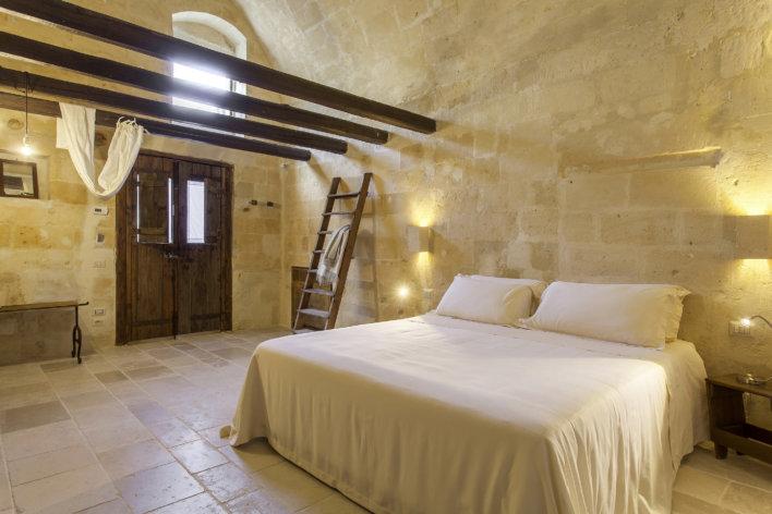 chambre lit double linge blanc et poutres apparentes