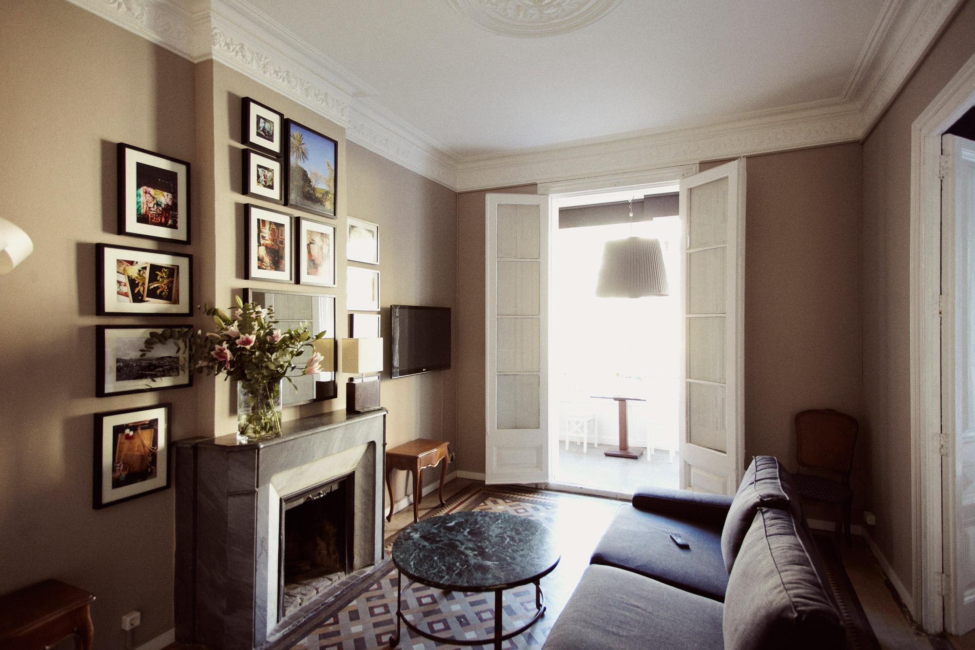 Salon de chambre d'hôtel comportant une cheminée surmontée de cadres décoratifs avec canapé et table basse en marbre.