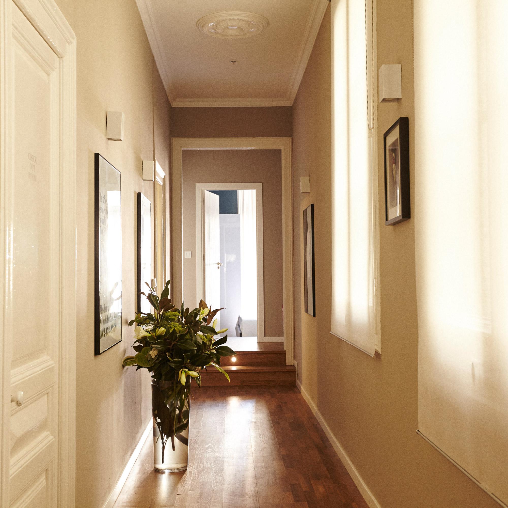 Couloir de style moderne dans des couleurs claires avec parquet au sol décoré de cadres au murs, avec un grand vase fleuri posé à même le sol.