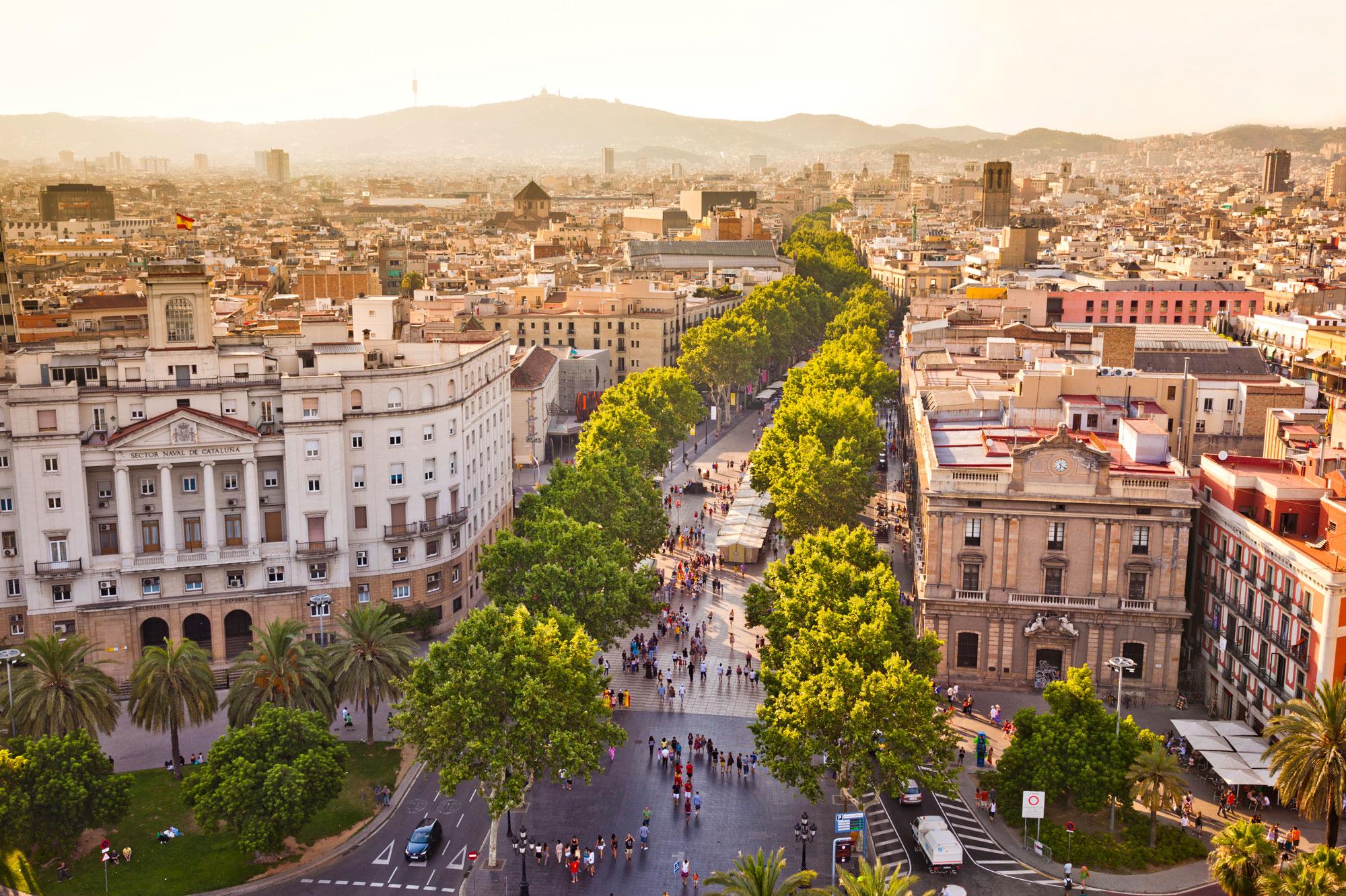 La Rambla de Barcelone foulée par quelques personnes au soleil couchant.