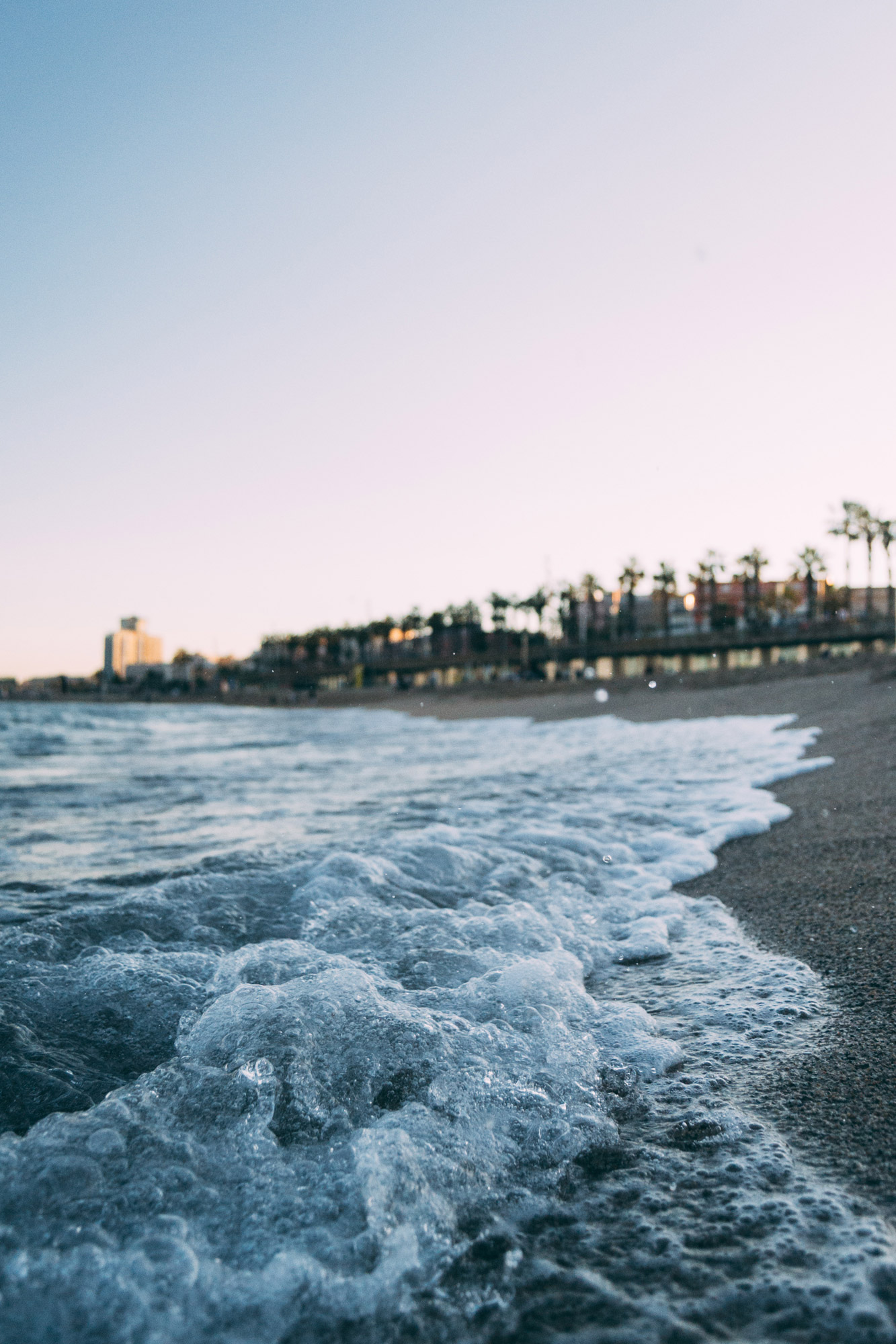 Gros plan sur l'écume des vagues qui s'échoue sur la plage avec les habitations en arrière-plan.