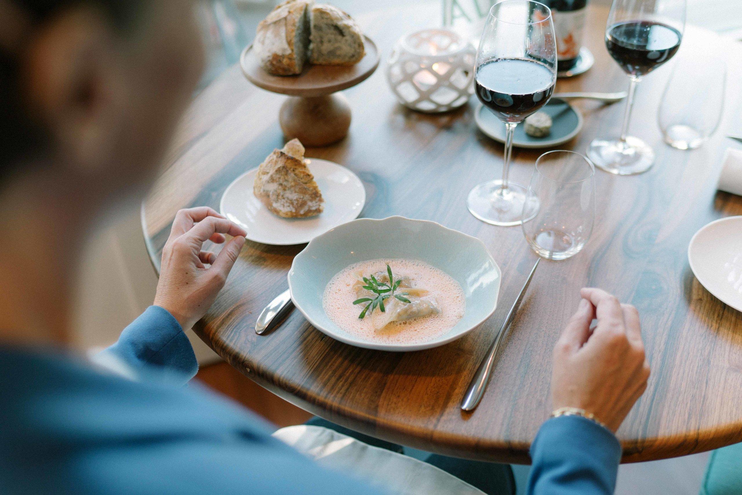 plat de langoustines sur table dressée avec miche de pain et verre de vin rouge
