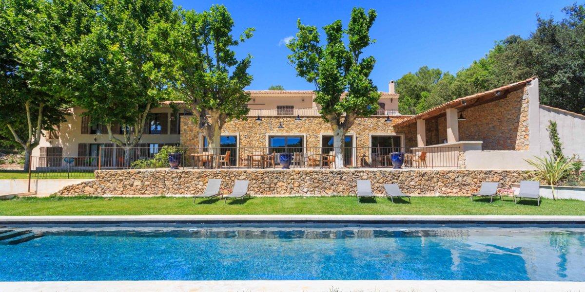 piscine extérieur devant bâtisse provençale et transats