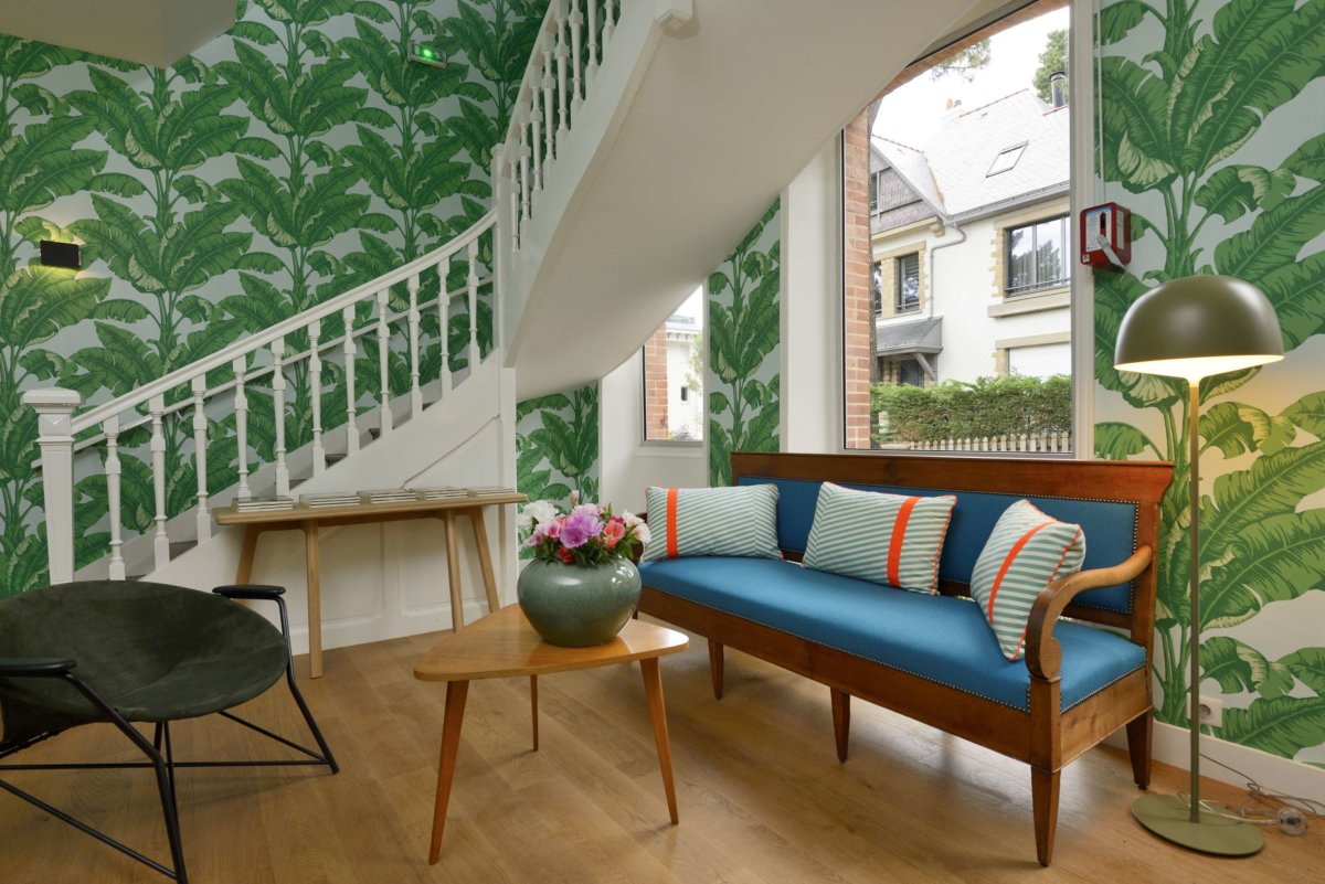 Hall avec escalier blanc en angle, canapé vintage bleu velours et bois, éléments décoratifs style scandinave