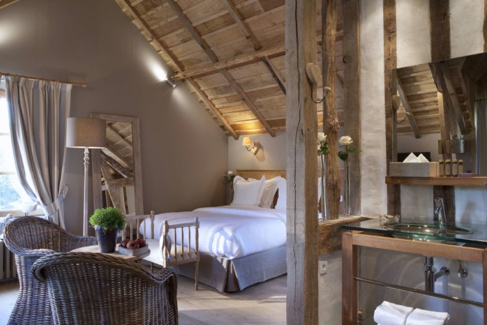 Chambre lit double poutres apparentes et décoration bois