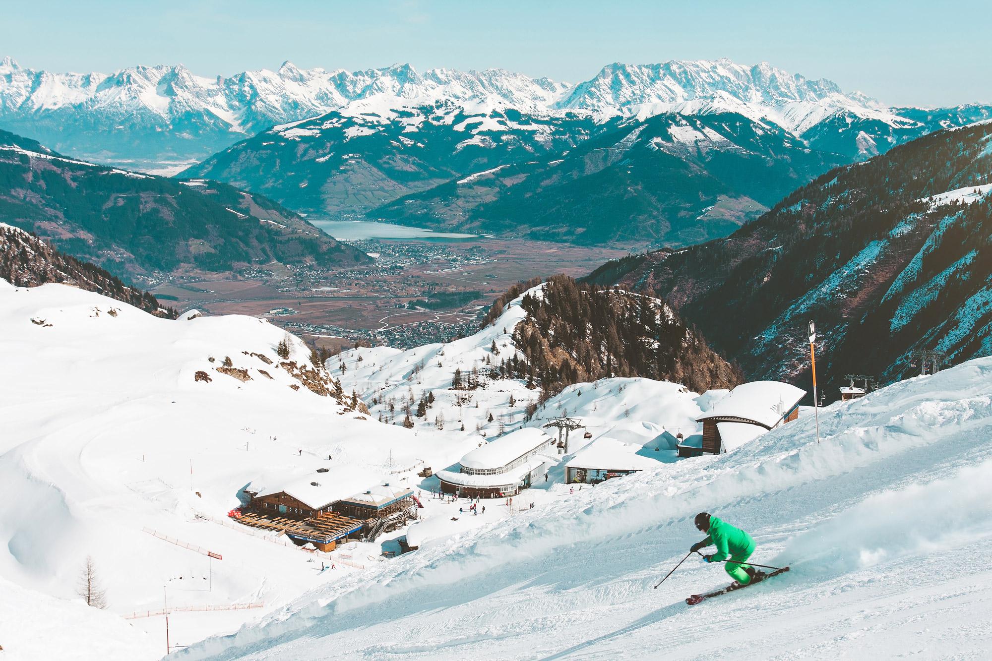 Skieur en combinaison verte en train de decsendre une piste enneigée en Autriche.