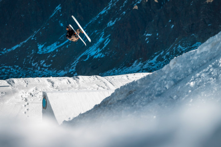 Homme en train de faire une pirouette avec ses skis dans un snowpark d'Autriche.