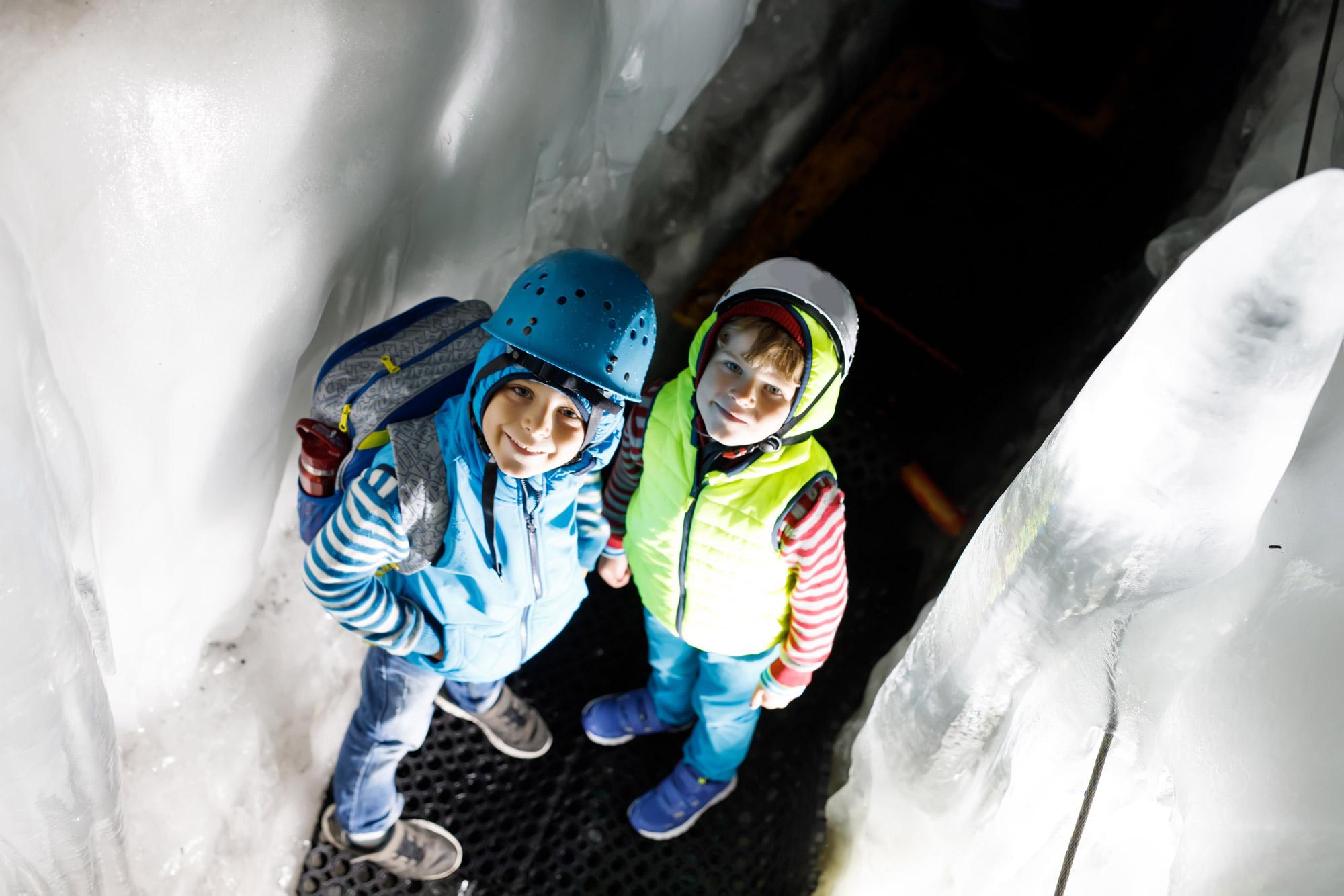 Deux jeunes enfants équipés pour faire de la randonnée en train de se balader au milieu de glaciers en Autriche.