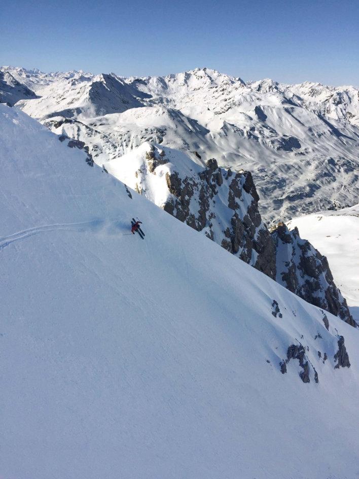 Sommets enneigés avec skieur en pleine descente.