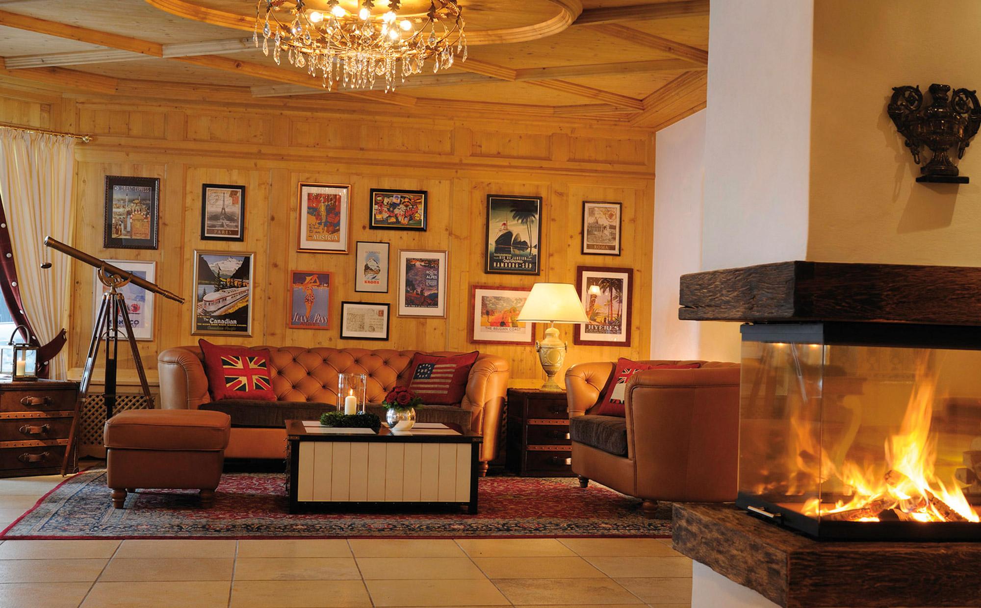 Salon cosy avec canapé chesterfield et cheminée ardente.