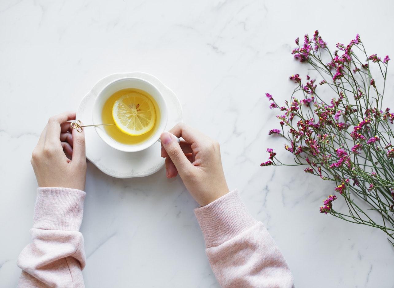 Tasse de thé avec tranche de citro et bras de femme avec pull over rose, bouquet de fleur sur le côté