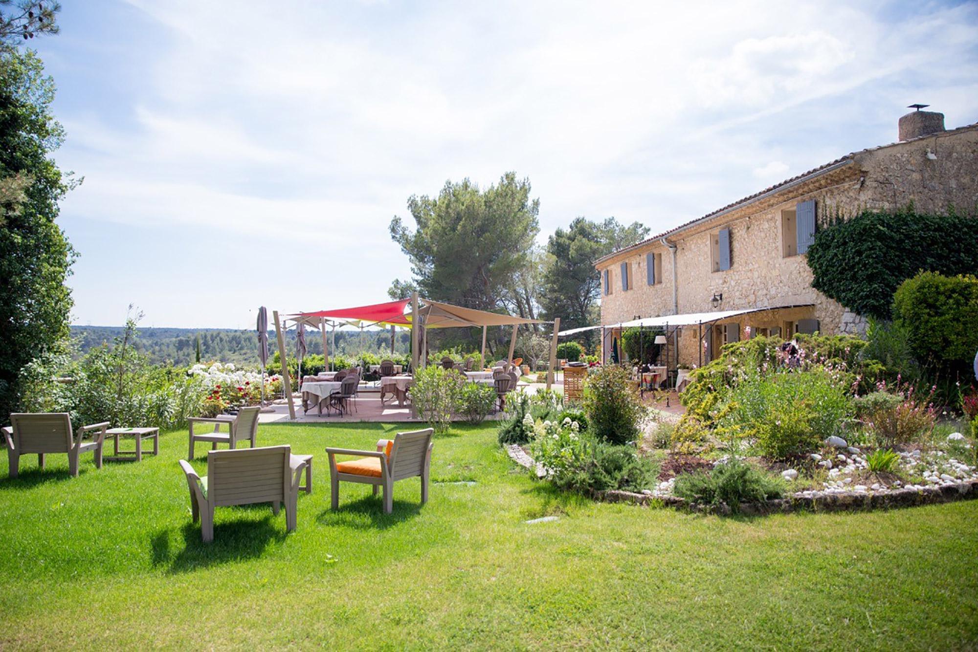 Jardin avec mobilier en bois, large pelouse et terrasse couverte à côté d'un Mas provençal