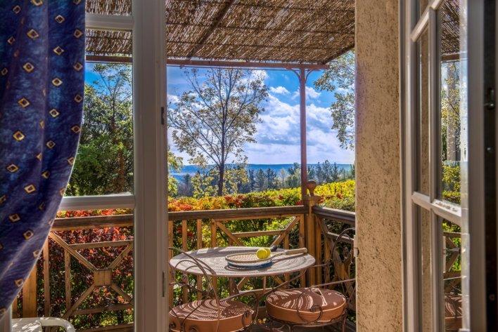 Vue sur un balcon terrasse avec table et deux chaises en fer forgé, vue dégagée