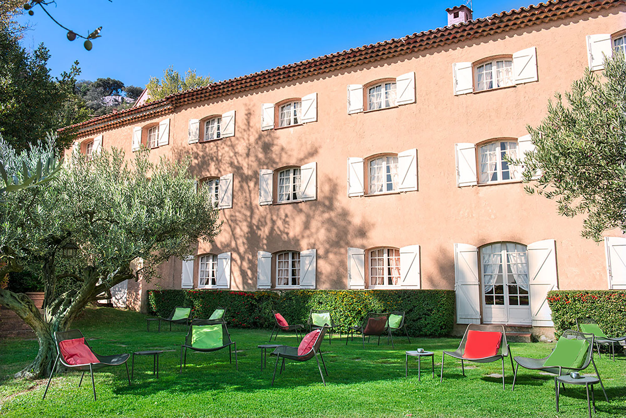 Façade couleur rose poudré, jardin avec chaise pliante et oliviers