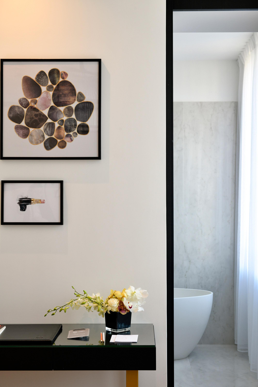 Détail décoration cadre, vase fleur jaune, porte ouverte sur un bout de baignoire design