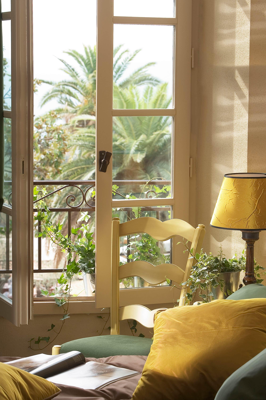 Photo détail décoration chaise et lampe de chevet jaune, devant fenêtre ouverte vue palmier