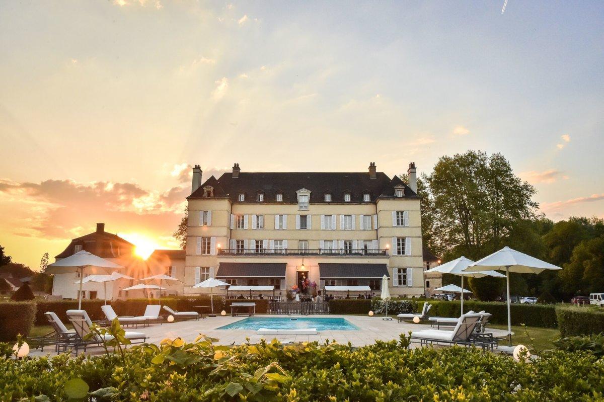 Façade château et piscine extérieure avec coucher de soleil