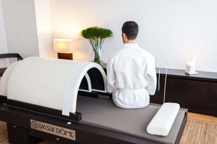 Homme en peignoir blanc sur un banc de soin spa