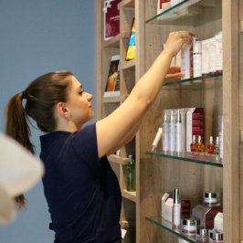 Praticienne spa qui réorganise les produits dans une étagère
