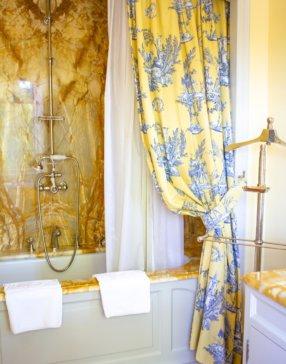 Salle de bain baignoire aux couleurs or et blanc