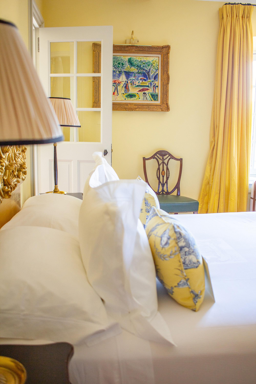 Détail lit chambre double mur jaune et linge blanc