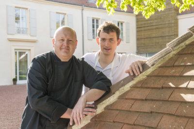 photo de deux chefs contre un toit en ardoises ocre