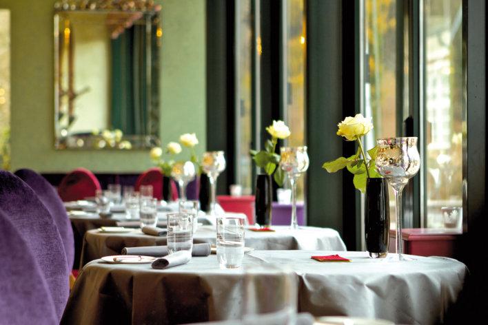 Salle de restaurant avec détail sur plusieurs tables dressées sur lesquelles sont posés des bouquets de fleurs