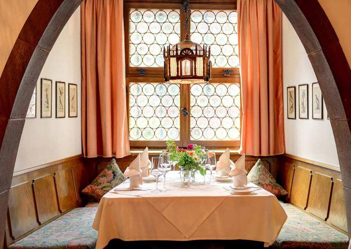 Table nappée rose, quatre couverts devant une vitre vitraux