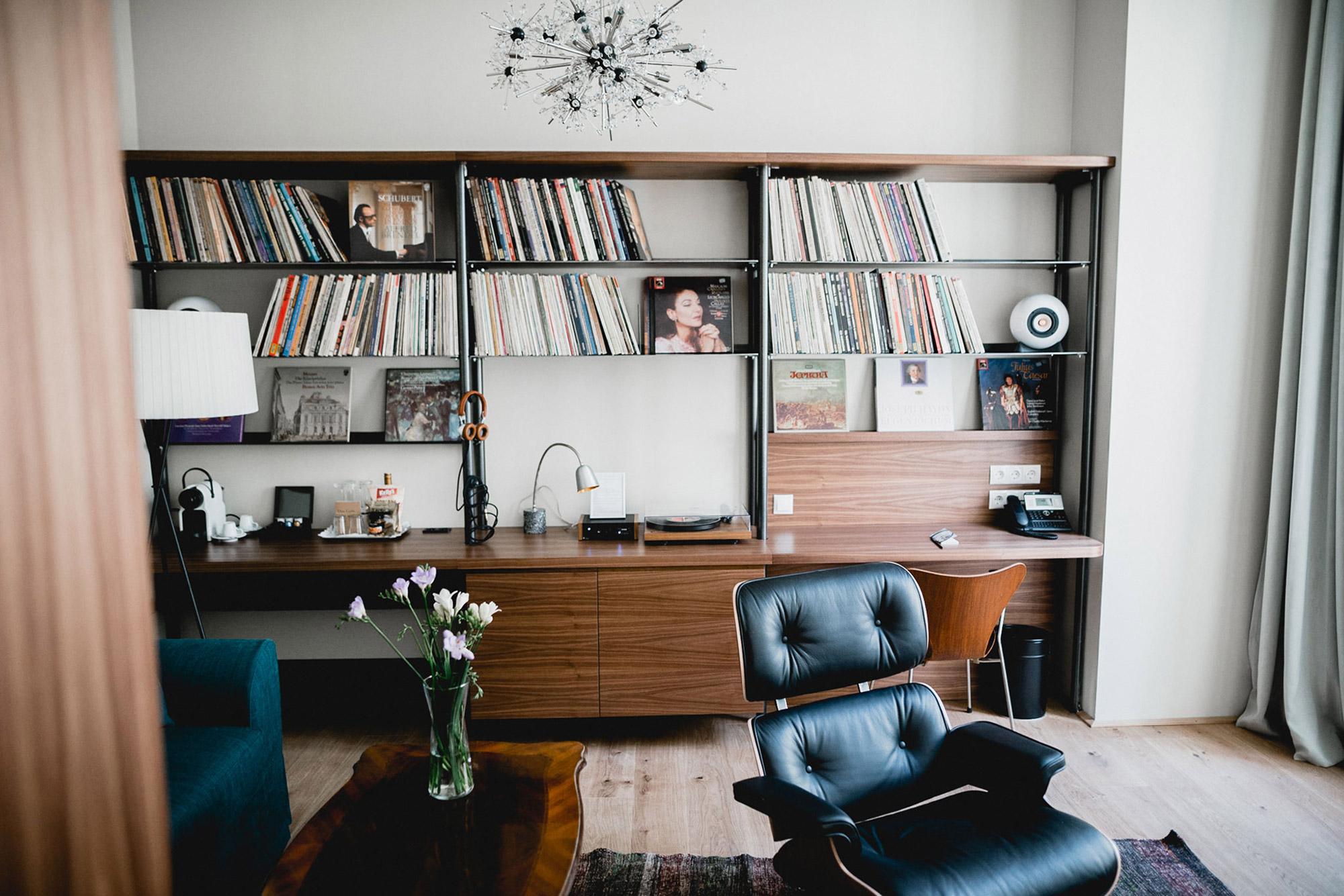 Salon vintage avec meuble en formica marron et fauteuil cuir capitonné bleu pétrole