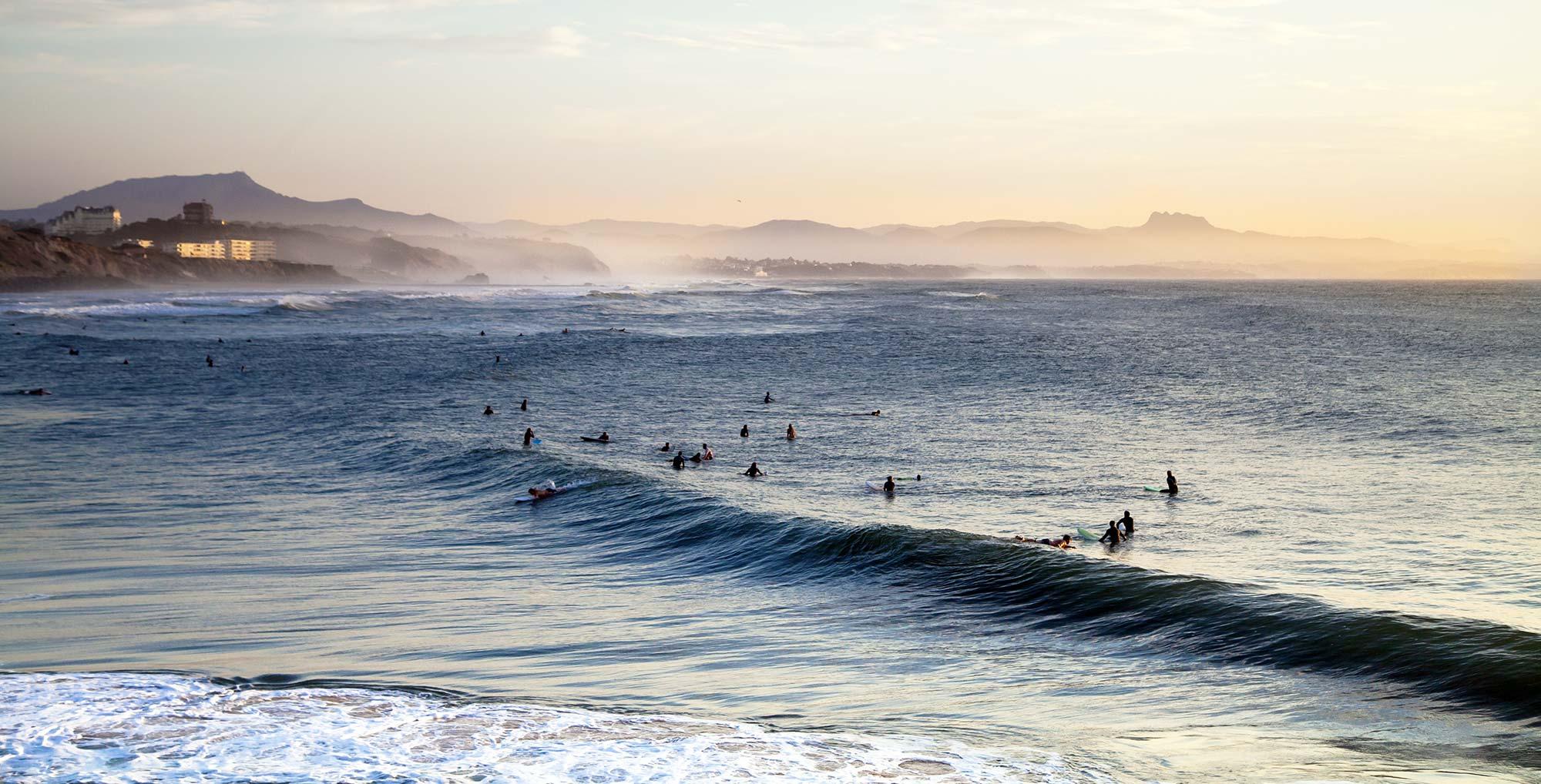 Surfeur sur une vagues et montagne en arrière plan