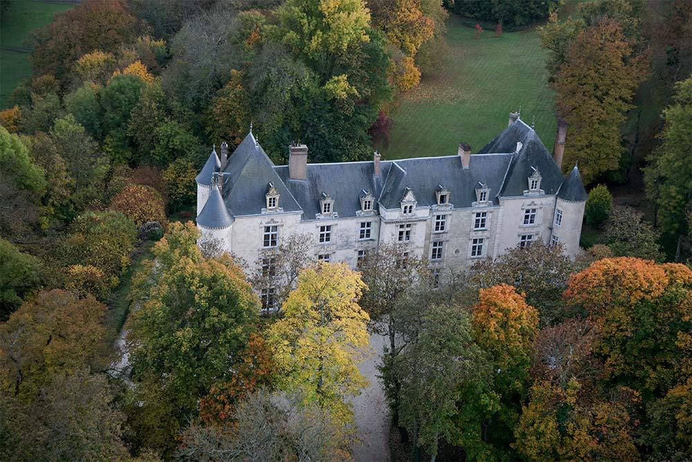 Château niché au milieu d'arbres couleurs d'automne